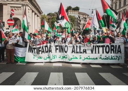 "MILAN, ITALY - JULY 26: People show a banner with the writing ""intifada till victory"" while marching and protesting against Gaza strip bombing in solidarity with Palestinians on JULY 26, 2014 in Milan - stock photo"