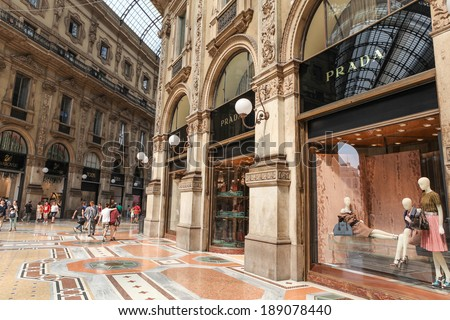 MILAN, ITALY - JULY 9, 2013: Prada Store in Galleria Vittorio Emanuele II shopping mall in Milan, with shoppers and tourists strolling around. Prada is an Italian luxury fashion house founded in 1913 - stock photo