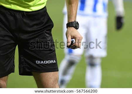 MILAN, ITALY-JULY 06, 2016: referee holds a whistle during the italian serie a soccer match at the san siro soccer stadium, in Milan.