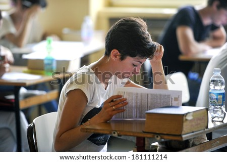 MILAN, ITALY-JUNE 20, 2012: College students seat on school desk in the exam room, for the secondary school's final exams, at the Artemisia Gentileschi School in Milan. - stock photo