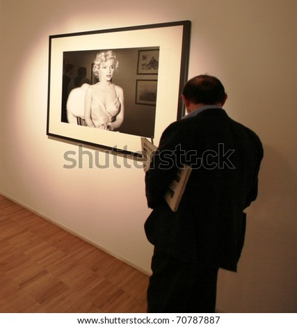 MILAN, ITALY - JUNE 16: People look at Phil Stern photography collection during his 'On the scene' exhibition opening at Forma Photography Foundation June 16, 2010 in Milan, Italy. - stock photo