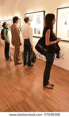 MILAN, ITALY - JUNE 16: People look at Phil Stern photos during exhibition opening at Forma Photography Foundation June 16, 2010 in Milan, Italy. - stock photo