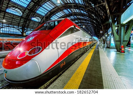 MILAN, ITALY - JUNE 07, 2012: Trenitalia Frecciarossa (red arrow) on Milan Central Station. This high speed train can reach 300 km/h and operate Turin-Milan-Bologna-Florence-Rome-Naples route. - stock photo