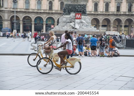 MILAN, ITALY - JUNE18: two bikes girl friend black race and caucasian blond traveling in summer shorts in profile on area wiht many tourist people background on JUNE 18, 2014 in Milan. - stock photo