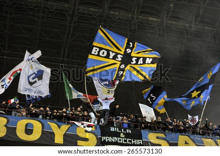 MILAN, ITALY- MARCH 19, 2015: FC Internazionale soccer fans waving flags during the UEFA Europa League match FC Internazionale vs Wolfsburg, at the San Siro stadium, in Milan - stock photo