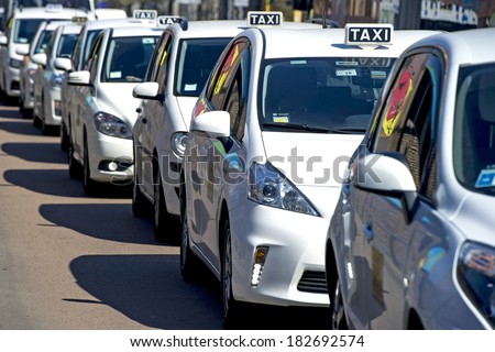 MILAN, ITALY-MARCH 19, 2014: Taxi cabs row on the taxi line, during a public transport strike, in Milan.