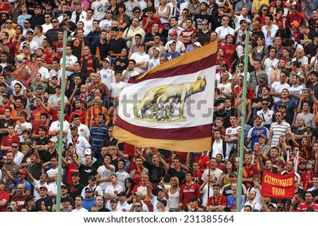 MILAN, ITALY-MAY 18, 2007: AS Roma soccer fans waving flags to support their team, during the soccer match, FC Internazionale vs AS Roma, in Milan. - stock photo