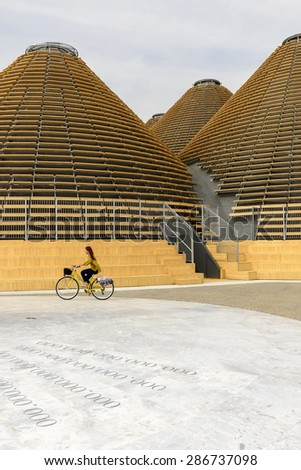 MILAN, ITALY - May 7: EXPO 2015, a cycling visitor  passes by wooden domes of Expo Centre building , shot  on may 7 2015  Milan, Italy  - stock photo