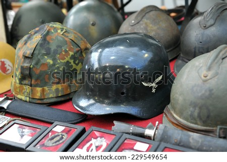 MILAN, ITALY - NOV 1: Helmets and miscellaneous items, Exhibitor sitting in his stand at Militalia, exhibition dedicated to militaria collectors and military associations on November 1, 2014 in Milan. - stock photo