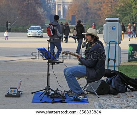 MILAN, ITALY - NOVEMBER 29, 2015: man in cowboy hat is playing guitar in parco Sempione, Milan - stock photo