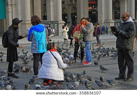 MILAN, ITALY - NOVEMBER 29, 2015: people are making photos on square nearle Milan cathedral