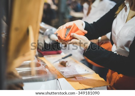 MILAN, ITALY - NOVEMBER 7: People visiting Eat Market, a street food parade with international dishes  in Milan on November, 7 2015. Salesman serving an italian cannolo to a customer