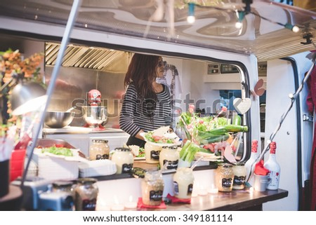 MILAN, ITALY - NOVEMBER 7: People visiting Eat Market, a street food parade with international dishes  in Milan on November, 7 2015. Woman inside her food truck waiting for customer