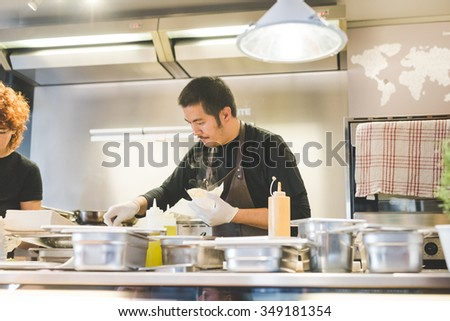 MILAN, ITALY - NOVEMBER 7: People visiting Eat Market, a street food parade with international dishes  in Milan on November, 7 2015. Chef of El Caminante stand cooking for customer