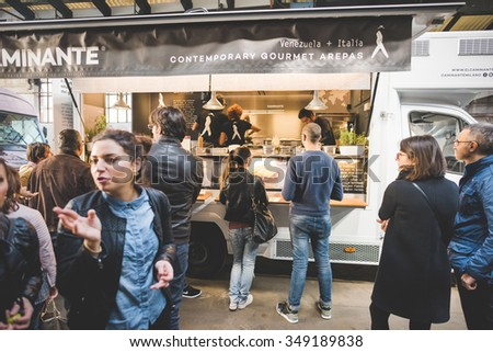 MILAN, ITALY - NOVEMBER 7: People visiting Eat Market, a street food parade with international dishes in Milan on November, 7 2015. People being served by El Caminante food truck at Eat Market - stock photo