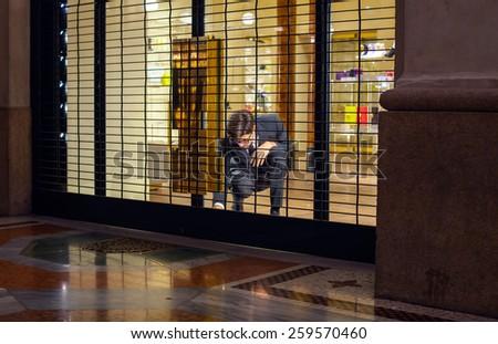 MILAN, ITALY - NOVEMBER, 24: Salesman close shop shutter on November 24, 2014 - stock photo