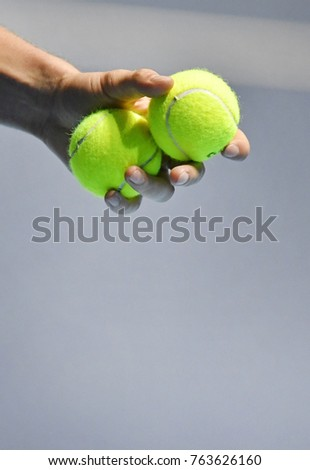 MILAN, ITALY-NOVEMBER 07, 2017: tennis player close up hand holding yellow ball during the professional Next Gen ATP tournament, in Milan.