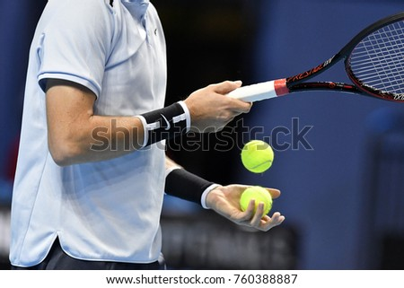 MILAN, ITALY-NOVEMBER 07, 2017:  tennis player close up hands holding yellow tennis ball, during the professional Next Gen ATP tournament, in Milan.