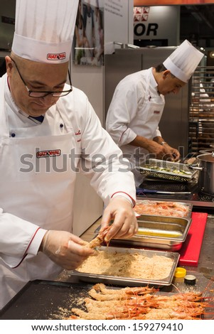 MILAN, ITALY - OCTOBER 18: A cook prepares red prawns at Host 2013, international exhibition of the hospitality industry on OCTOBER 18, 2013 in Milan. - stock photo