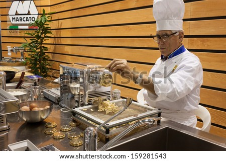 MILAN, ITALY - OCTOBER 18: Cook prepares handmade pasta at Host 2013, international exhibition of the hospitality industry on OCTOBER 18, 2013 in Milan.
