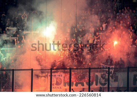 MILAN, ITALY-OCTOBER 23, 2014: french soccer fans lighting smoke flares at san siro stadium, during the Europa League match FC Internzionale vs ST Etienne, in Milan. - stock photo