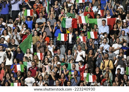 MILAN, ITALY-OCTOBER 10, 2014: italian team fans cheering and waving national flags during the indoor female volleyball match Italy vs Russia during the Volleyball World Cup, in Milan. - stock photo