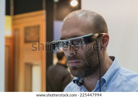 MILAN, ITALY - OCTOBER 22: Man wearing glasses for augmented reality at Smau, international exhibition of information communications technology on OCTOBER 22, 2014 in Milan. - stock photo