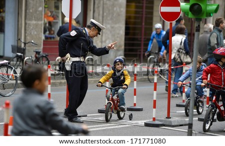 MILAN, ITALY - OCTOBER 14: Policeman teaches children to recognize traffic signals, during a sunday with no cars allowed in the streets of Milan, October 14, 2012 - stock photo