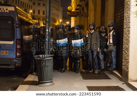 MILAN, ITALY - OCTOBER 11: Policemen beside the Turkish consulate watch demonstrators protesting and asking help for Kurdish people in Syria on OCTOBER 11, 2014 in Milan. - stock photo