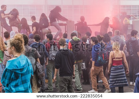 MILAN, ITALY - OCTOBER 10: Students climb over the fence of the education agency building to protest against money cuts in the public school on OCTOBER 10, 2014 in Milan. - stock photo