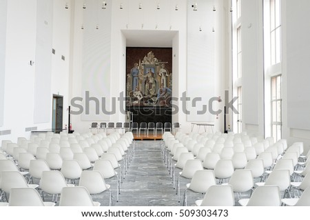 MILAN, ITALY-OCTOBER 28, 2016: white plastic design chairs on a conference room at the Triennale Palace, design and architecture museum, in Milan.