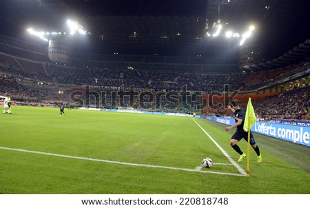 MILAN, ITALY-SEPTEMBER 24,2014: brazilian FC Internazionale's player Dodo', prepares to kick a corner, with a panoramic view of San Siro stadium at night, during a serie A match, in Milan.