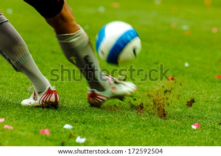 MILAN, ITALY - SEPTEMBER 29: Italian professional Serie A soccer match in Milan September 29, 2006. A football player close up kicking the ball with the green pitch on the background.