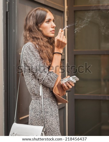 MILAN, ITALY - SEPTEMBER 19: Model smokes outside Missoni fashion shows building for Milan Women's Fashion Week on SEPTEMBER 19, 2014 in Milan.