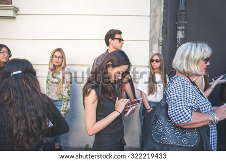 MILAN, ITALY - SEPTEMBER 25: People during Milan Fashion week, Italy on SEPTEMBER 25, 2015. Eccentric and fashionable asiatic woman using smartphone waiting for models and vips at Milan fashion week