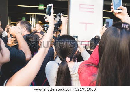 MILAN, ITALY - SEPTEMBER 25: People during Milan Fashion week, Italy on SEPTEMBER 25, 2015. Fans taking photo with smartphone at models and vips outside city during Milan fashion week