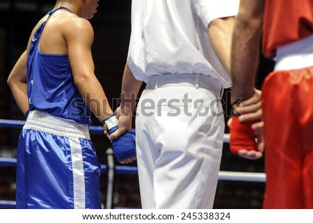 MILAN, ITALY-SEPTEMBER 04, 2009: referee holding amateur boxers hands waiting for the jury proclaiming the winner during the amateur world boxing championship, in Milan.