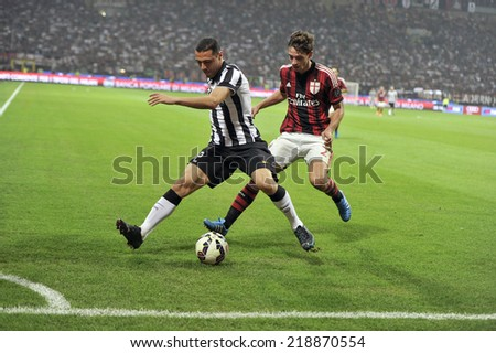 MILAN, ITALY-SEPTEMBER 20, 2014: soccer players Mattia De Sciglio and Romulo in action at the San Siro stadium, during the professional serie A soccer match AC Milan vs Juventus, in Milan. - stock photo