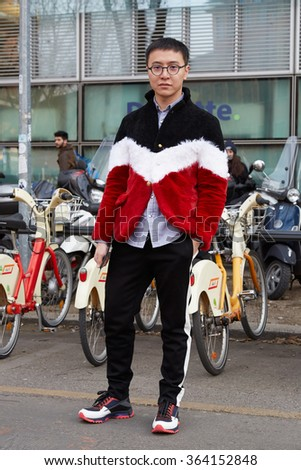 MILAN - JANUARY 18: Man with black, red, white, jacket poses for photographers before Emporio Armani fashion show on January 18, 2015 in Milan, Italy. Man fashion fall winter 2016 / 2017