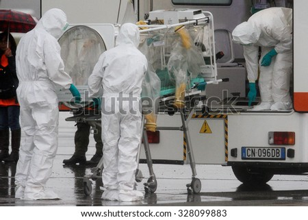"MILAN MALPENSA - NOVEMBER 12, 2014: Ebola emergency simulation in Malpensa. A bogus infected patient has arrived in the airport, and then carried to ""Sacco Hospital"" by a special modified ambulance."
