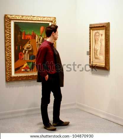 MILAN - MARCH 27: Man looks at paintings galleries during MiArt ArtNow, international exhibition of modern and contemporary art March 27, 2010 in Milan, Italy. - stock photo