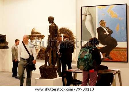 MILAN - MARCH 27: People look at paintings in exhibition at MiArt ArtNow, international exhibition of modern and contemporary art March 27, 2010 in Milan, Italy. - stock photo