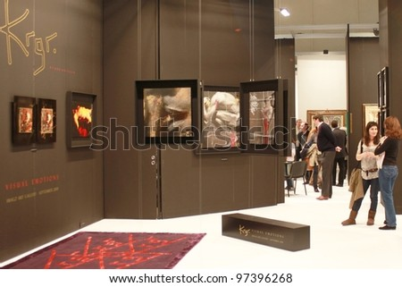 MILAN - MARCH 27: People walk trough paintings work of arts galleries during MiArt ArtNow, international exhibition of modern and contemporary art March 27, 2010 in Milan, Italy. - stock photo