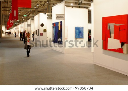 MILAN - MARCH 26: People walk trough paintings work of arts galleries during MiArt ArtNow, international exhibition of modern and contemporary art March 26, 2010 in Milan, Italy. - stock photo