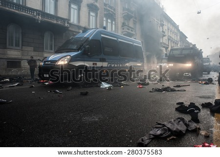 Milan, may 1, 2015 - Police vehicles passing upon hammers, batons, gas masks left by protesters on the road at the end of the violent protest in the day of the opening of Expo Milan 2015