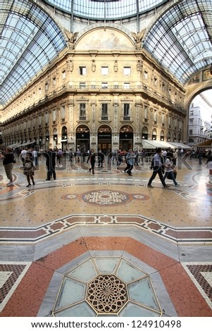 MILAN - OCTOBER 6: People visit Vittorio Emmanuele II shopping gallery on October 6, 2010 in Milan, Italy. Inaugurated in 1865, the gallery claims to be the oldest shopping center worldwide. - stock photo