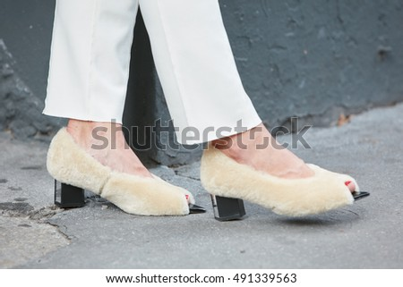 MILAN - SEPTEMBER 21: Woman with beige fur shoes and white trousers before Fay fashion show, Milan Fashion Week street style on September 21, 2016 in Milan.
