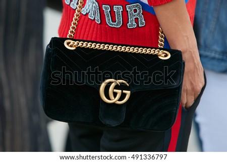 MILAN - SEPTEMBER 21: Woman with black velvet Gucci bag before Gucci fashion show, Milan Fashion Week street style on September 21, 2016 in Milan.