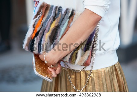 MILAN - SEPTEMBER 24: Woman with colorful fur bag and golden skirt before Jil Sander fashion show, Milan Fashion Week street style on September 24, 2016 in Milan.