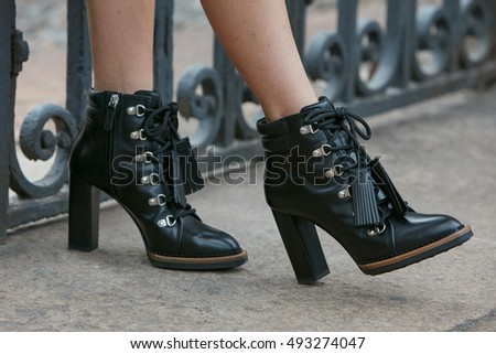 MILAN - SEPTEMBER 23: Woman with high heel black leather boots before fashion Tod's show, Milan Fashion Week street style on September 23, 2016 in Milan.